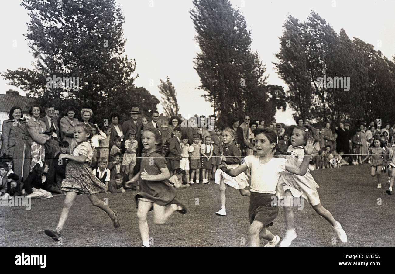 1950s, historical, young girls about to hit the finishing rope in the 60 yard dash at a primary school sports day, - Stock Image