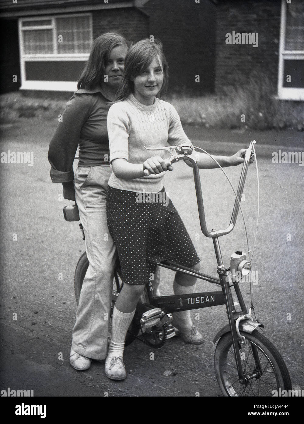 1970s, historical, two young girls stting outside on a Tuscan bike, a chopper type bicycle with high handlebars - Stock Image