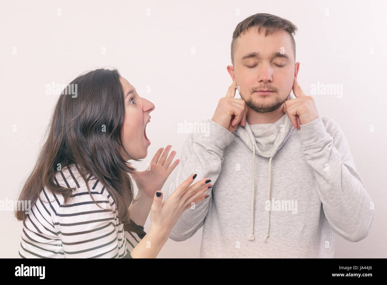 Woman yelling at her boyfriend in hysterics. Young man covers his ears, not wanting to listen to it - Stock Image