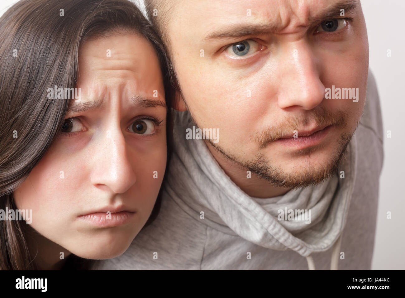 Young couple with dubious looks forward, wrinkling his face in disbelief. - Stock Image