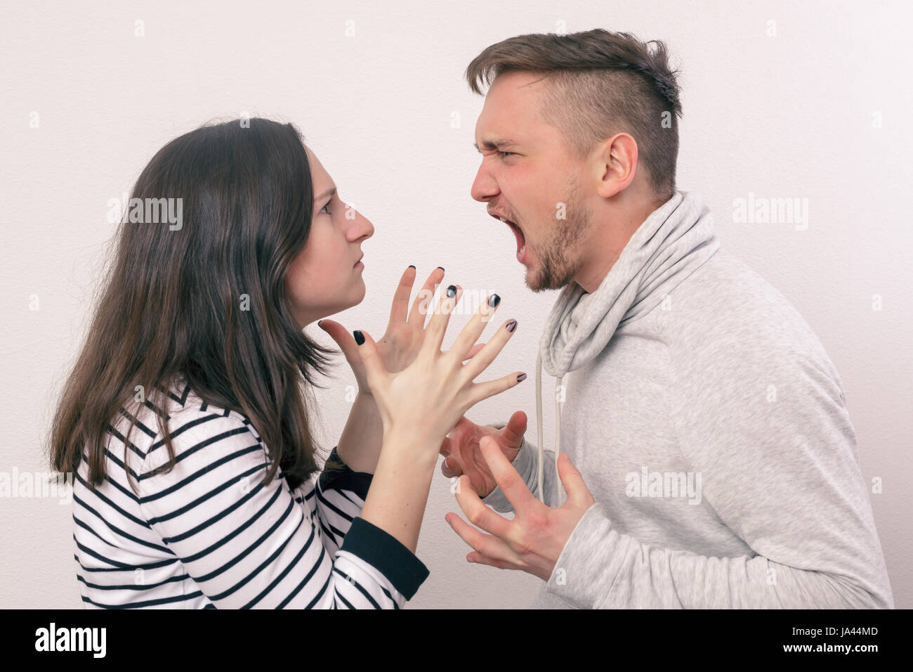 Young pair of lovers quarrel. Man and woman emotionally yelling at each other - Stock Image