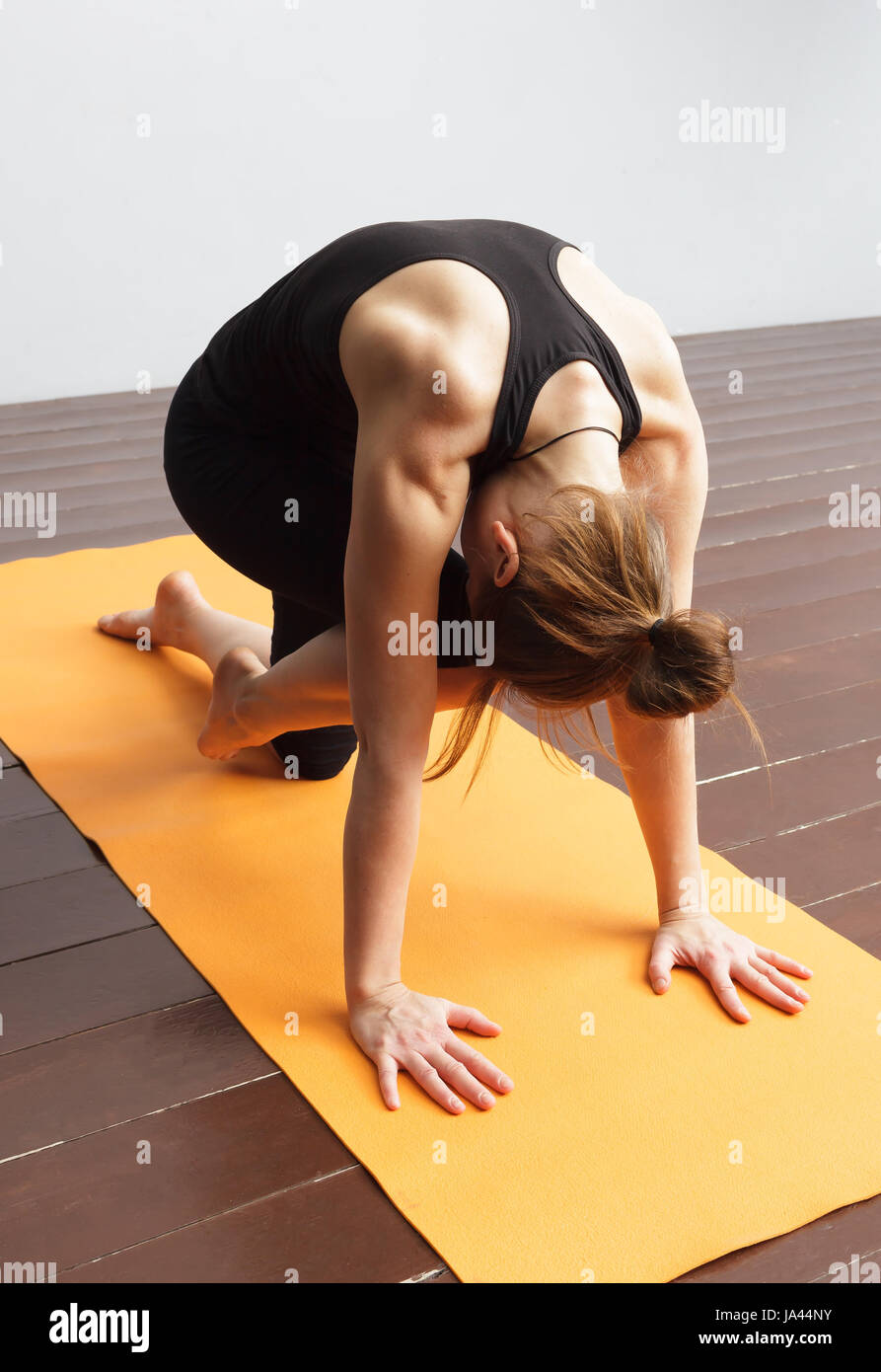 Girl doing a cat pose for the spine from yoga therapy. - Stock Image