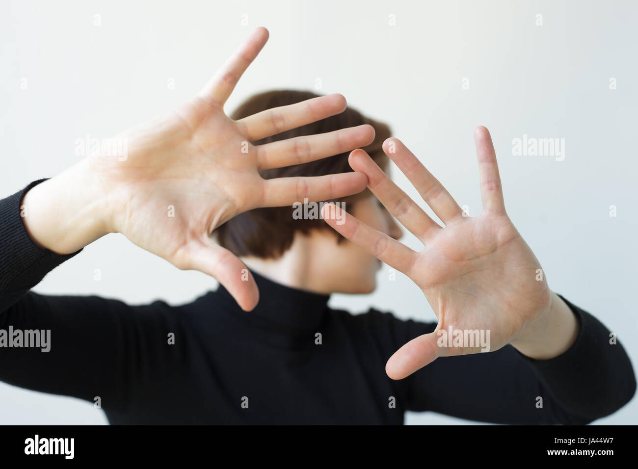 Girl turns aside, stretching her hands forward. Pushing someone away from contact - Stock Image