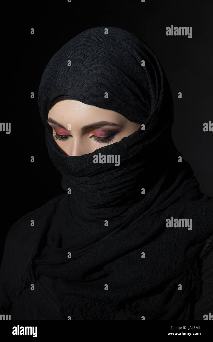 Beautiful muslim woman in niqab traditional veil against on dark background - Stock Image