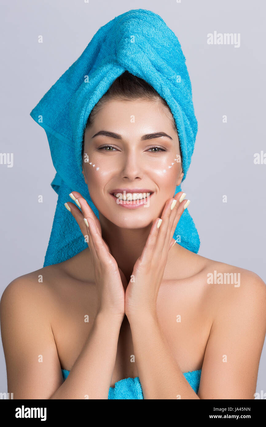Beautiful woman with towel on head applying creme after shower - Stock Image