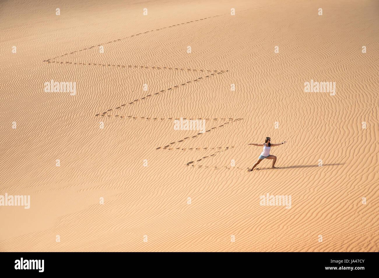 Beautiful woman hiking on giant sand dunes while making a zig zag pattern. Liwa desert, UAE. - Stock Image