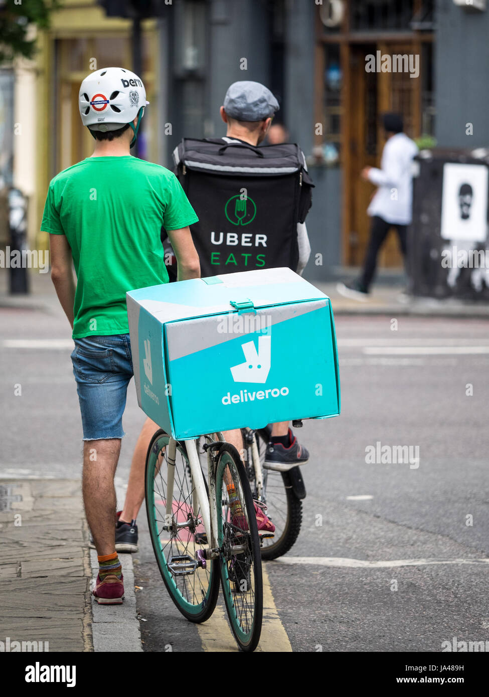 e86527d4e58 Deliveroo and Uber Eats food delivery bike couriers wait at traffic lights  while delivering food to