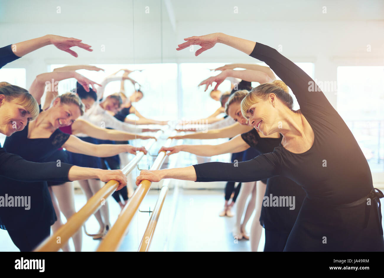 Cheerful mature ballerinas stretching with hands up standing at mirror in ballet class. Stock Photo