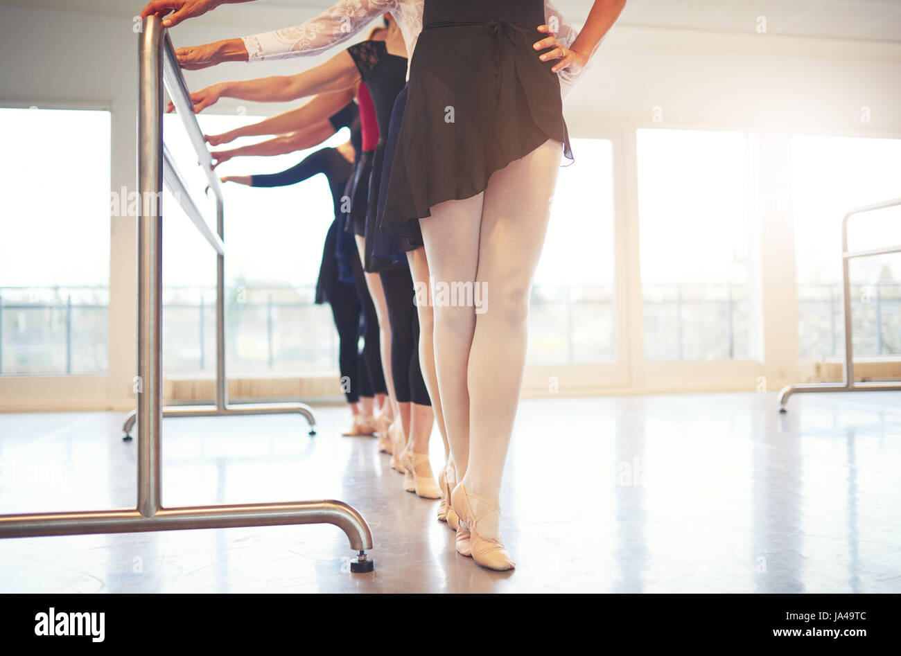 Legs of unrecognizable female ballet performers standing and doing gymnastics in the class. - Stock Image