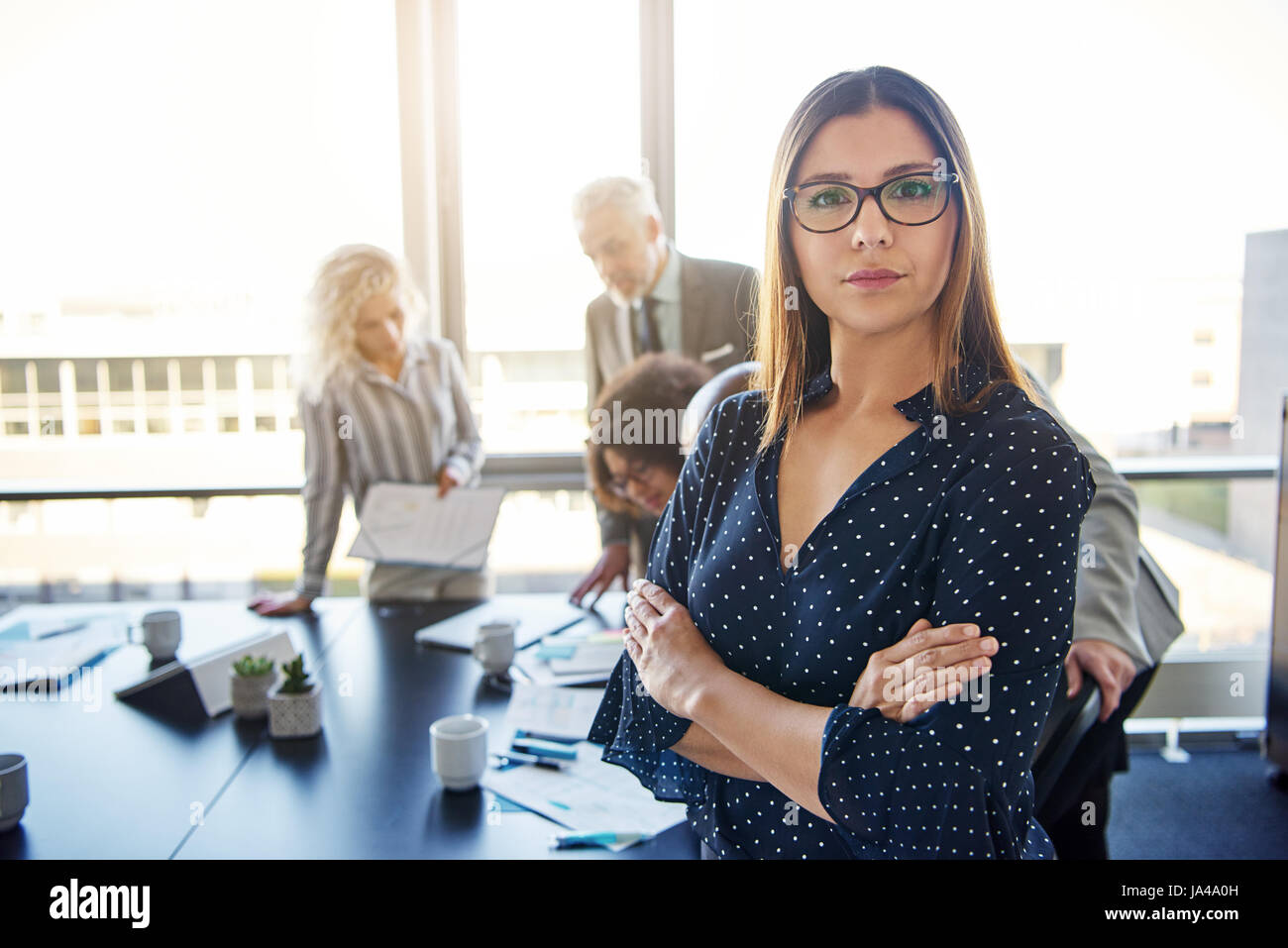 Serious business woman in front of team, looking at camera - Stock Image