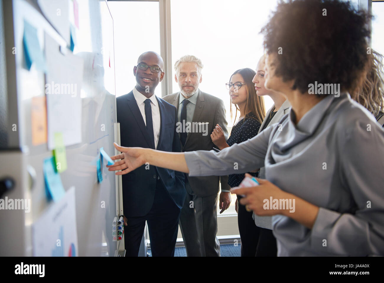 Group of mixed business people having a meeting using a white board in bright office space - Stock Image