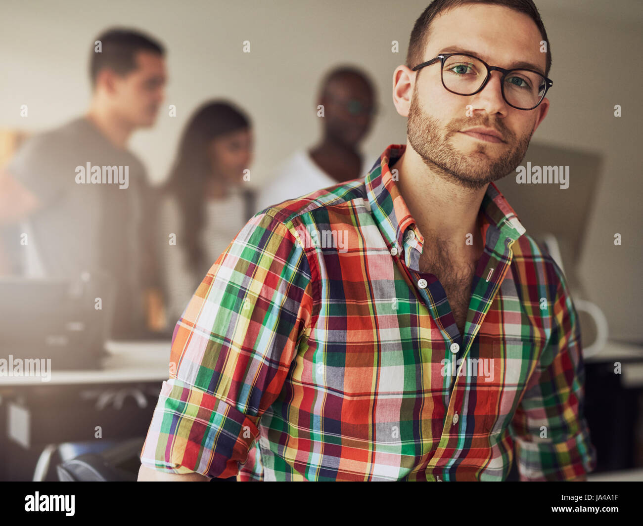 Modern businessman wearing casual clothes and glasses in the office. - Stock Image