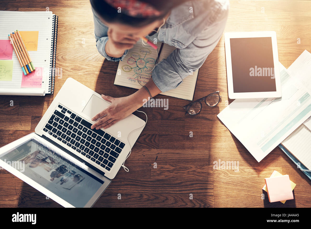From above entrepreneur woman browsing laptop and holding pencil while thinking at laptop in office. - Stock Image