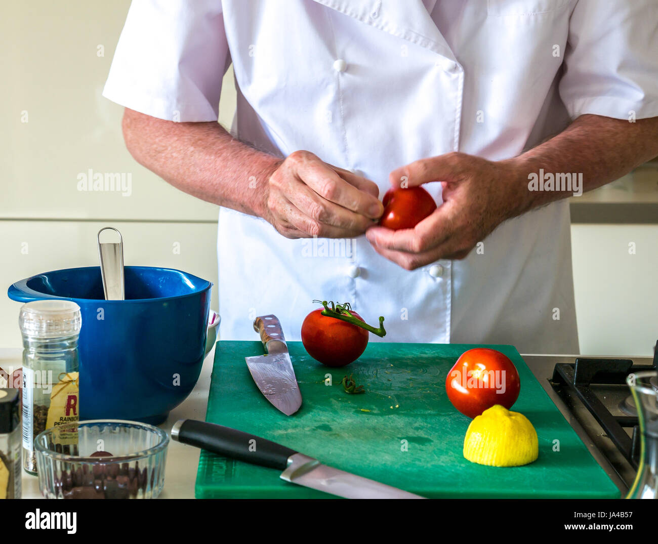 A man in chef whites preparing tomatoes on a green chopping board on a kitchen counter with other kitchen utensils - Stock Image