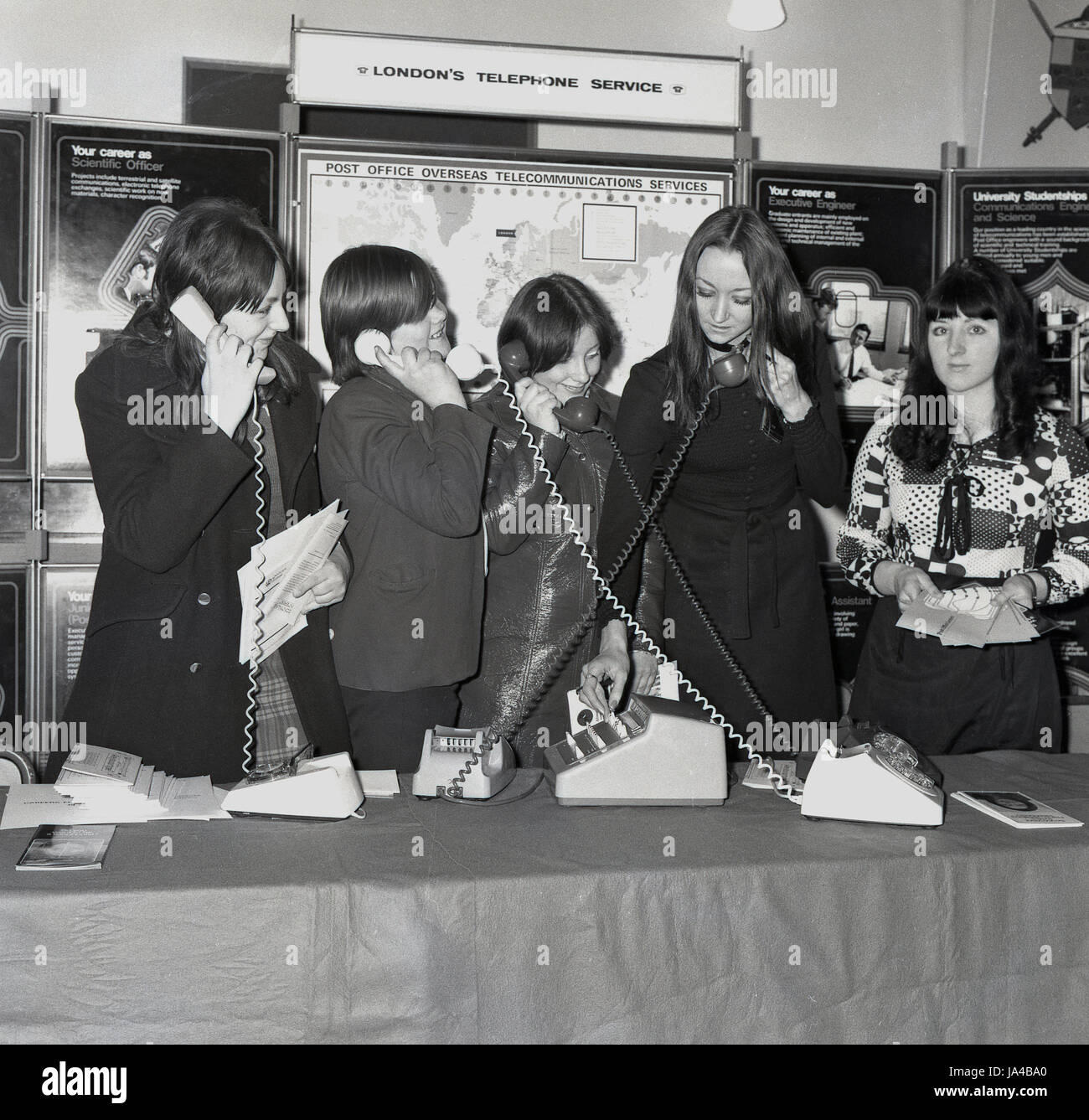 Late 1960s, historical, group of female students have fun with the different types of telephones on a Post Office - Stock Image