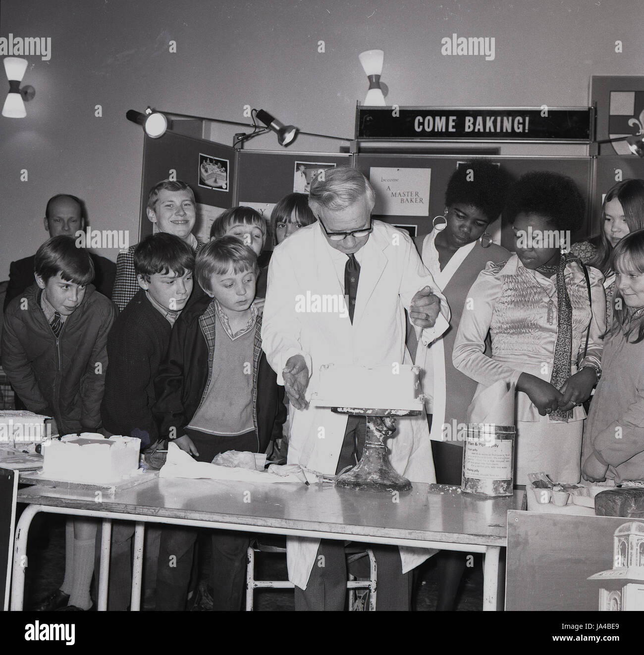 1960s, historical, group of school students at a career advise show, watch a demonstration at a baking stand, London, - Stock Image
