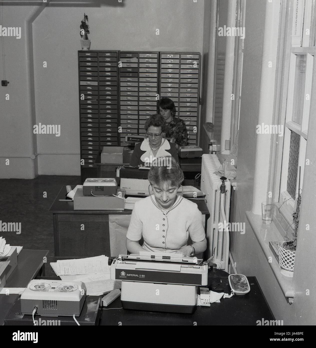 1970s, historical, three secretaries in a sparse office using audio equipment as they type up reports from dictaphone - Stock Image