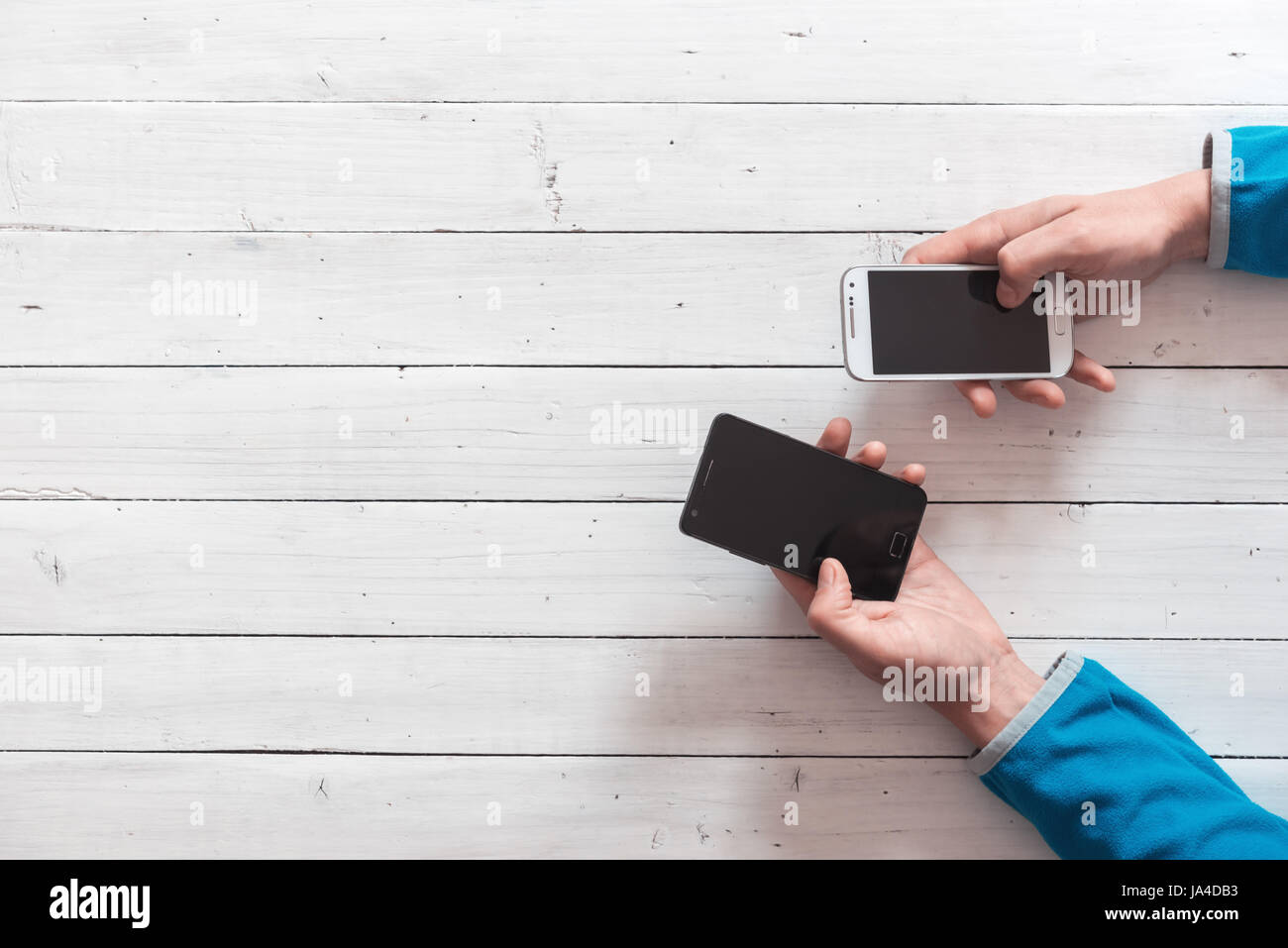 Mobile phones in hands closeup. Network addicted concept - Stock Image