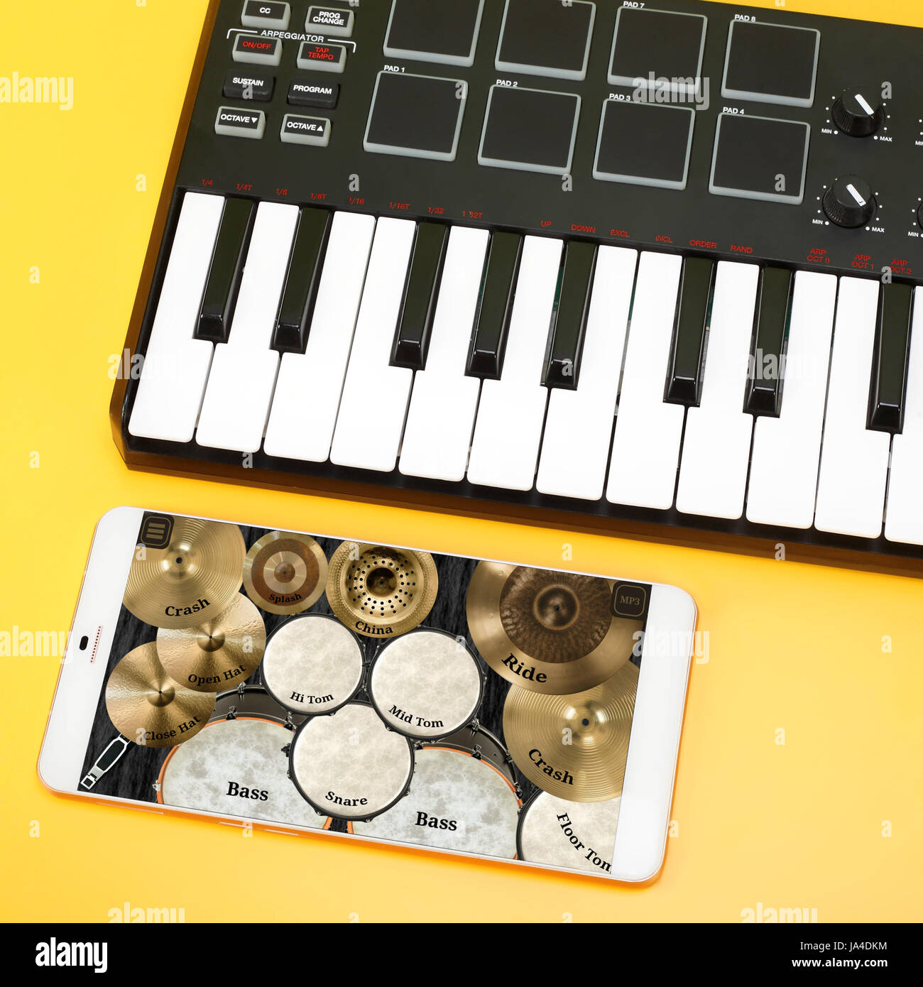 Musical instrument - MIDI keyboard and Drum kit on the smartphone screen for the composition of music. On a yellow - Stock Image