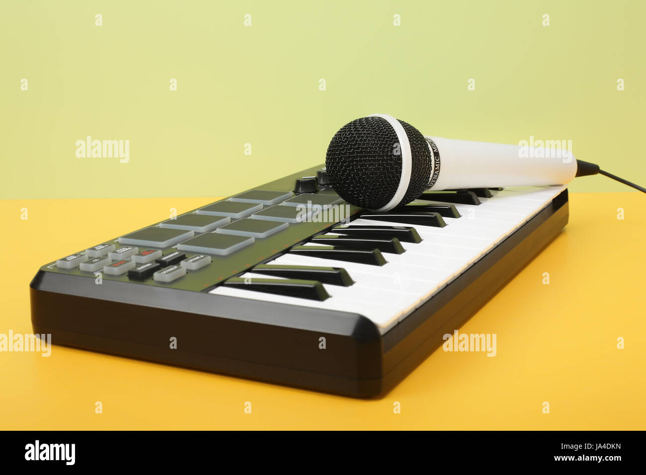 Musical instrument - MIDI keyboard and vokal microphone for a karaoke on a flavovirent background. - Stock Image
