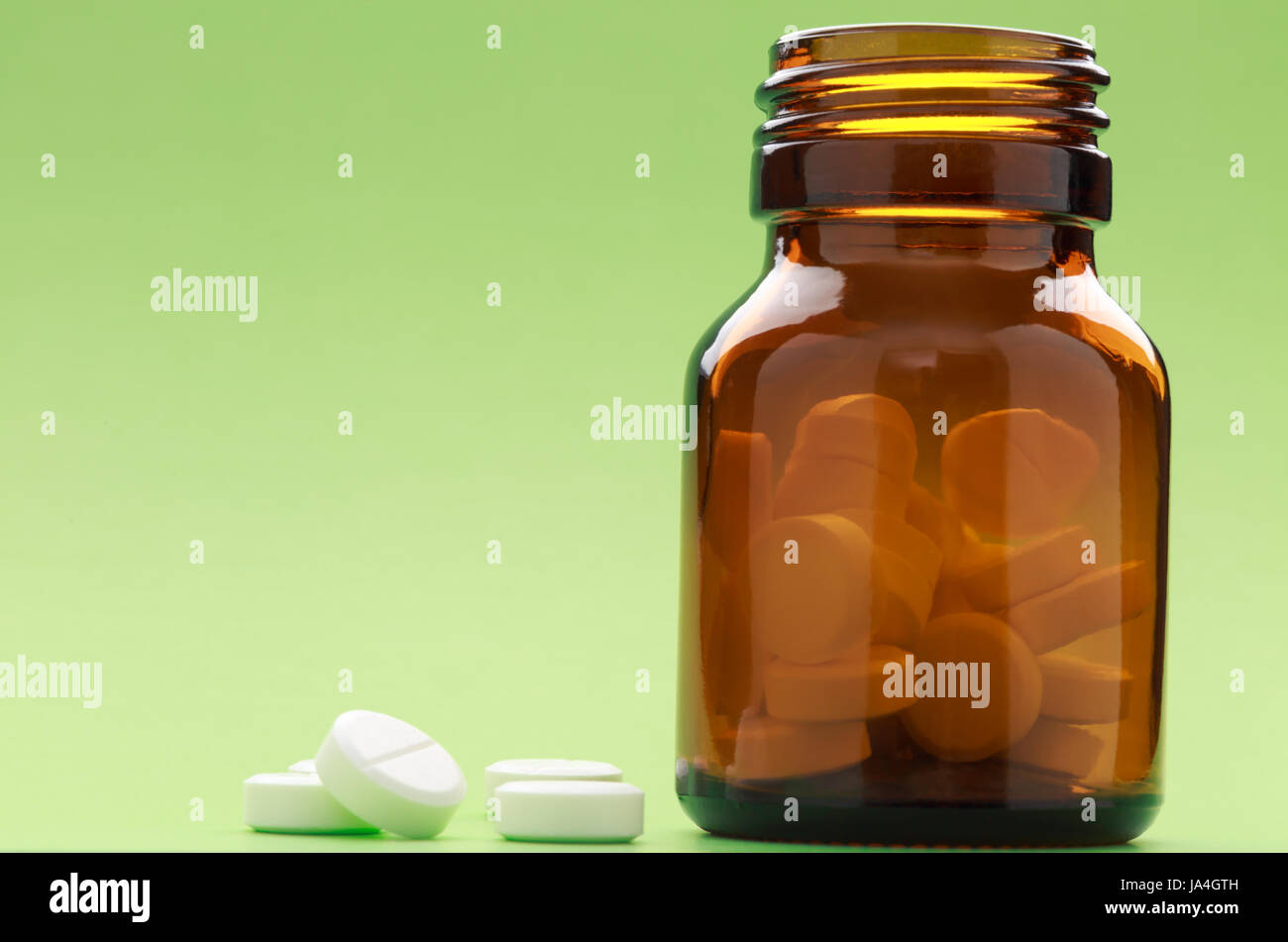 A bottle of brown-glass pills on a green background - Stock Image