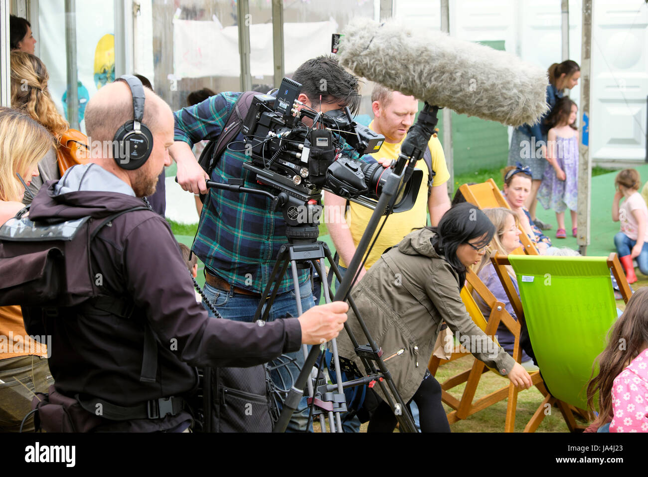 Video camera man and sound engineer with sound  boom filming people sitting on deckchairs at the Hay Festival, Hay - Stock Image