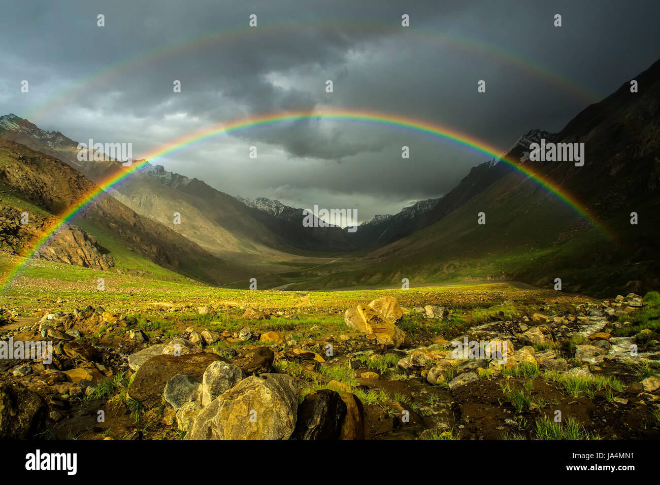 A double bright rainbow after the rain to the high mountains of the valley: above the green fields is a beautiful, Stock Photo