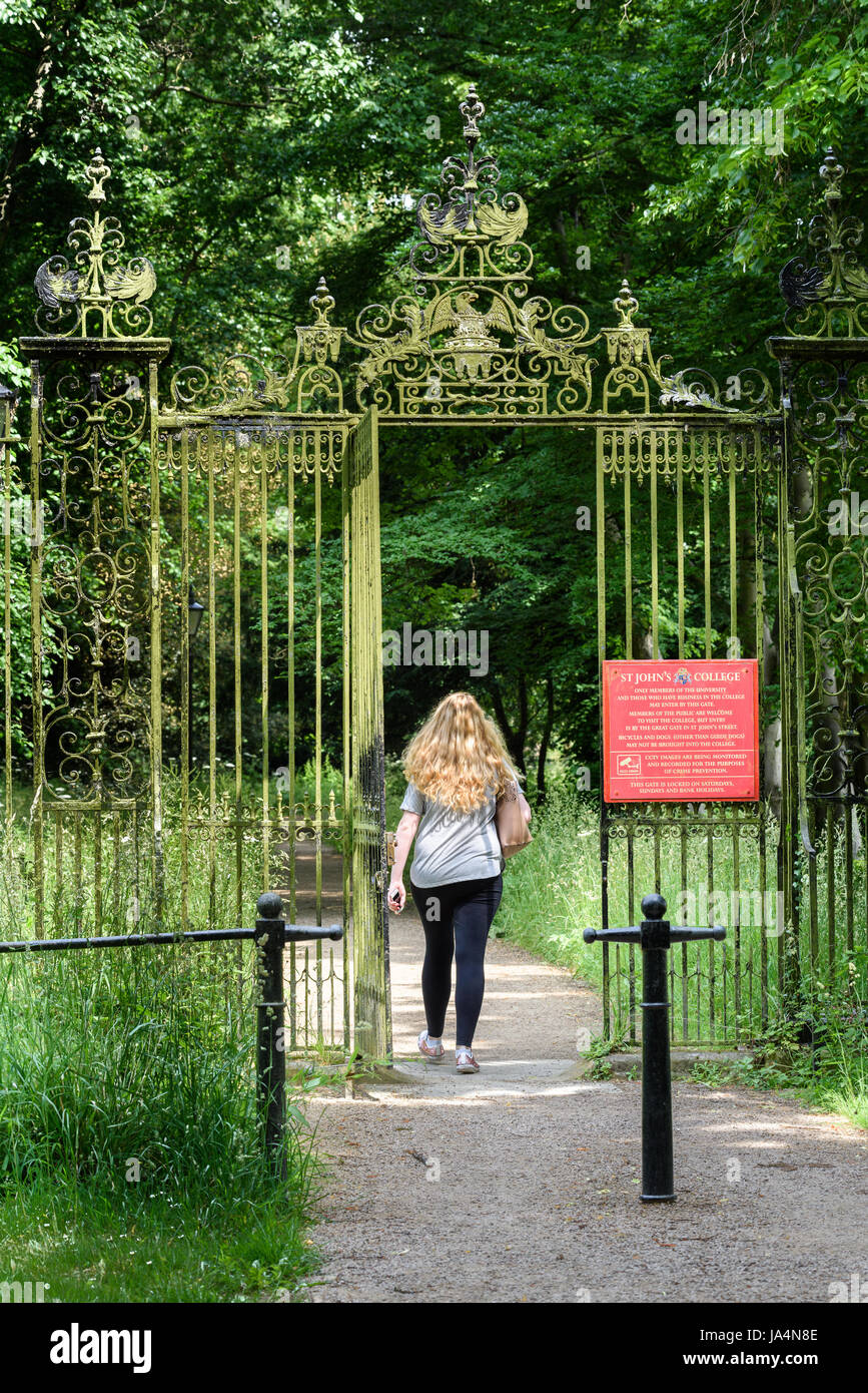 A female student passes through the entrance gate from the 'Backs' to St John's college, university of Cambridge, Stock Photo