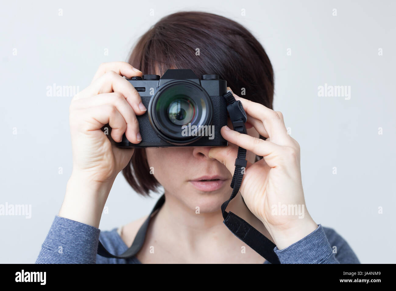 A girl is holding a camera by her face. The lens looks like a big eye. Hobby with photography Stock Photo