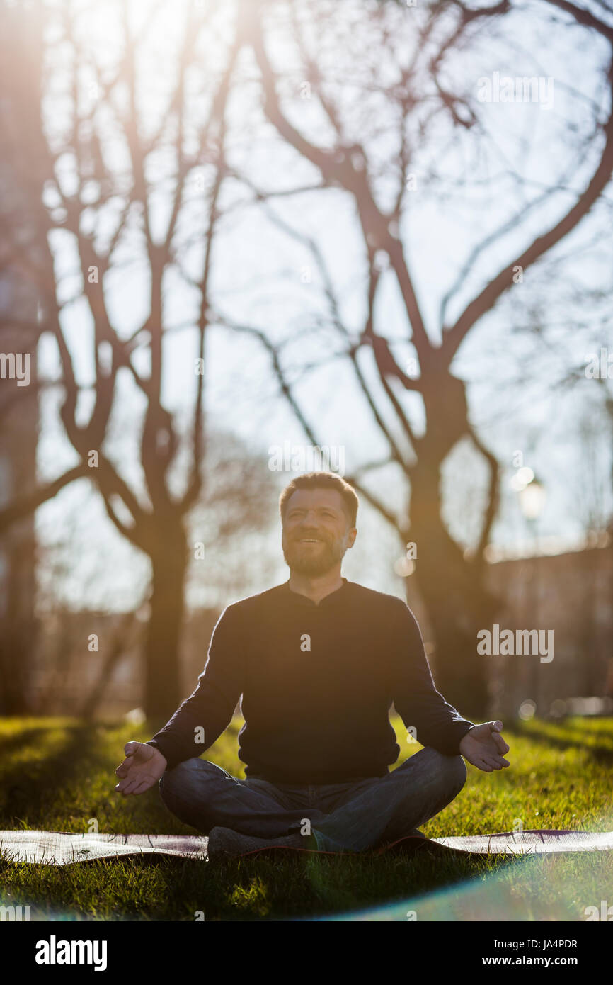 Mature man sitting on yoga mat in comfortable asana smiling and relaxing in park. Meditation in city life conditions - Stock Image