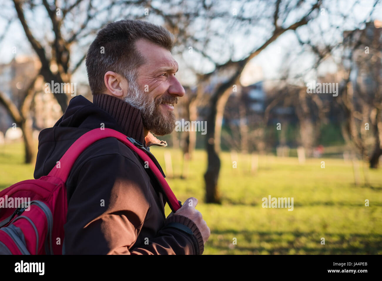 Mature man is walking in a park with a backpack on a sunny day and smiling. - Stock Image