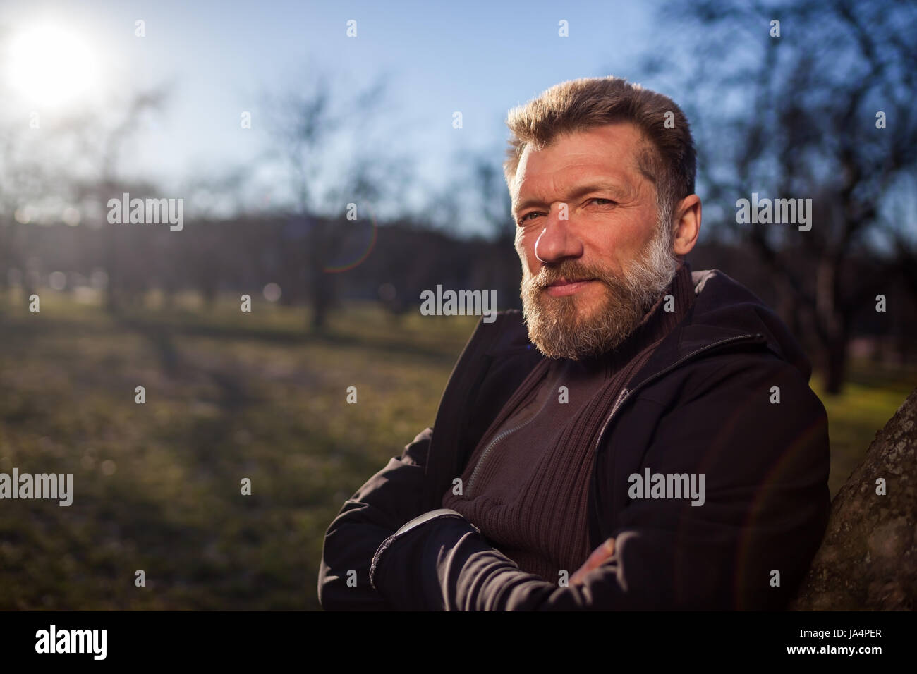 Portrait of an elderly man in a park. He looks thoughtfully into the distance, planning and dreaming about the future - Stock Image
