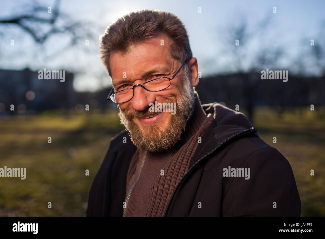 Portrait of a mature man in glasses on a background of nature. - Stock Image