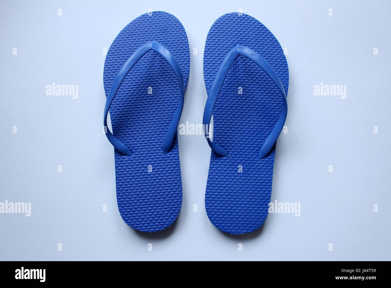 Pairs of beach shoes tong in colors on white background - Stock Image