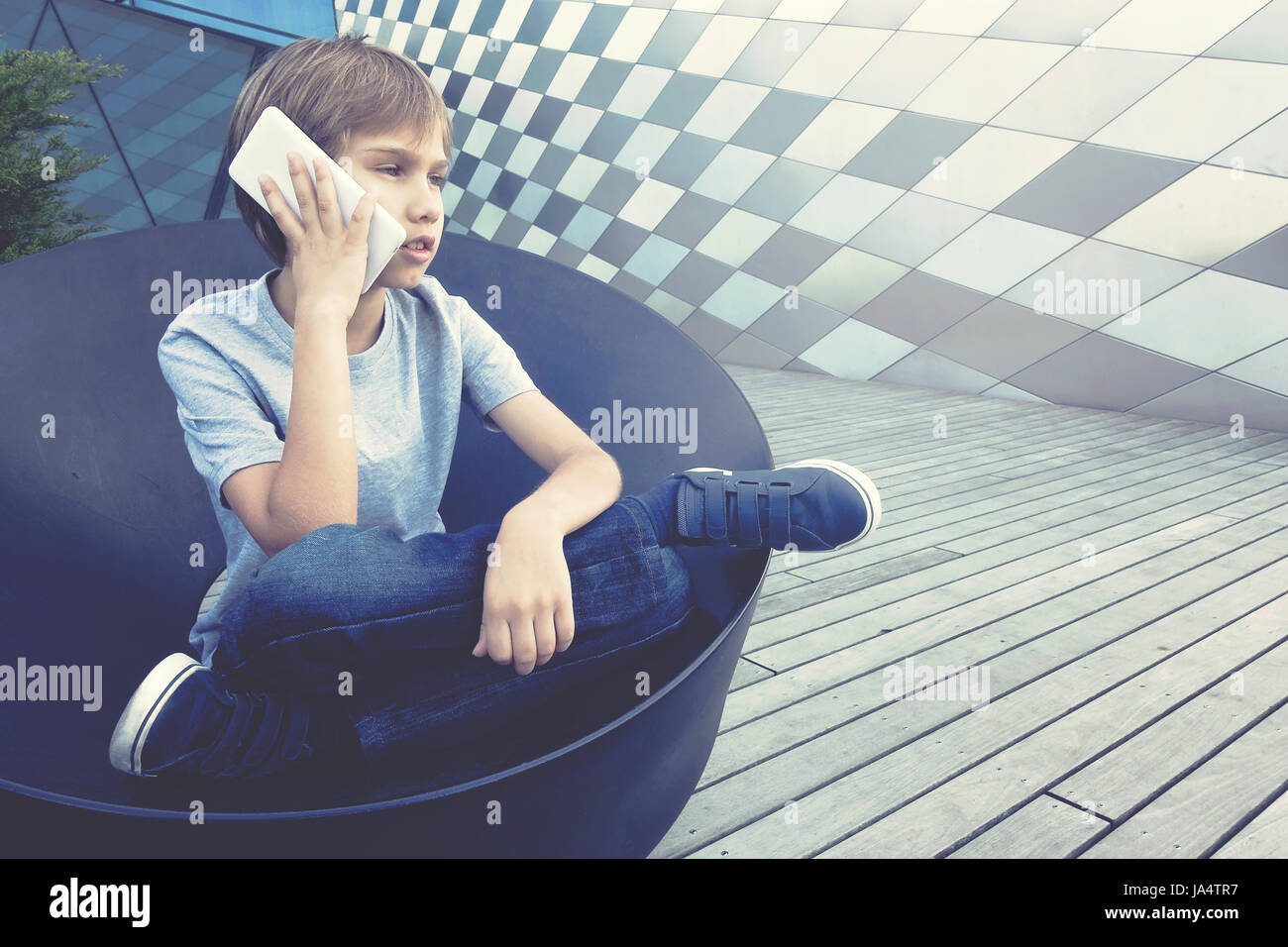 Boy talking on the mobile phone in the city - Stock Image