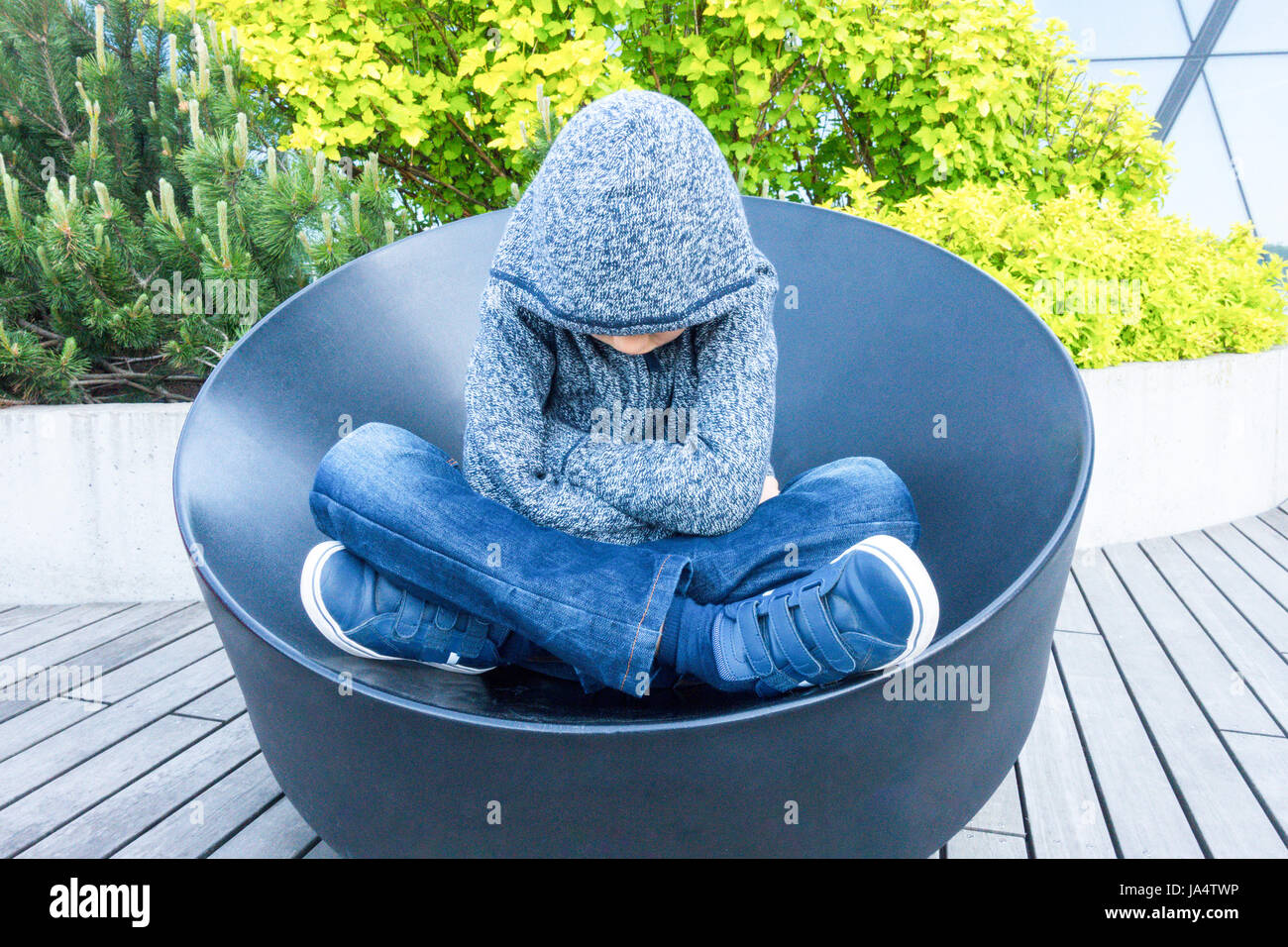 Sad, lonely, unhappy, disappointed child sitting outdoors - Stock Image