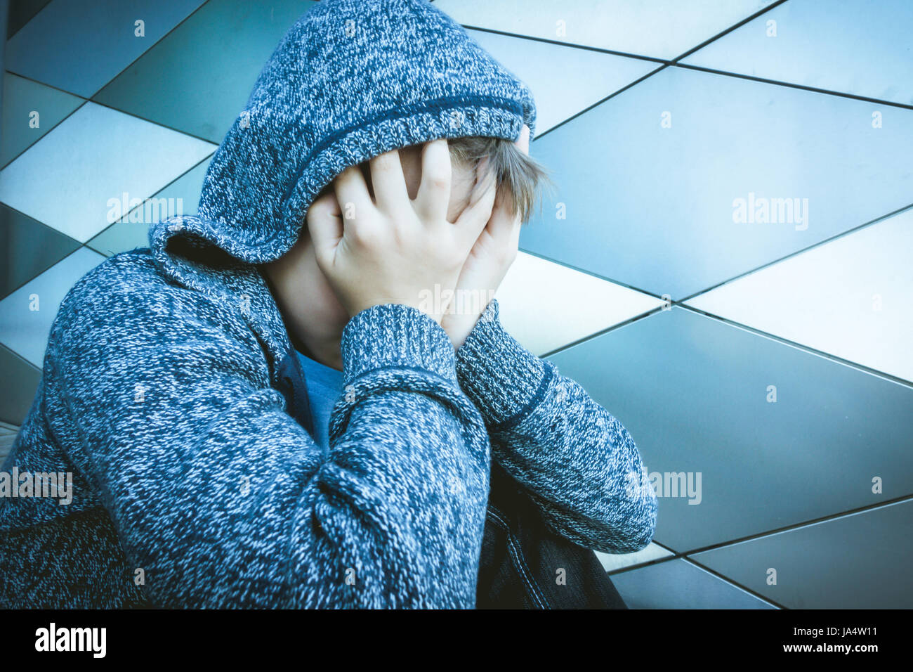 Sad, lonely, unhappy, disappointed child holding head with hands - Stock Image