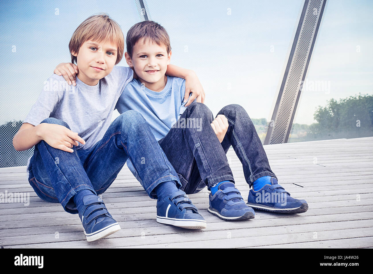 Two happy kids sitting together and embracing - Stock Image