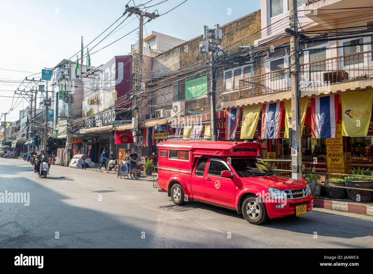 Traditional red songthaew taxi on a street in Chiang Mai. This is the largest city in northern Thailand. - Stock Image