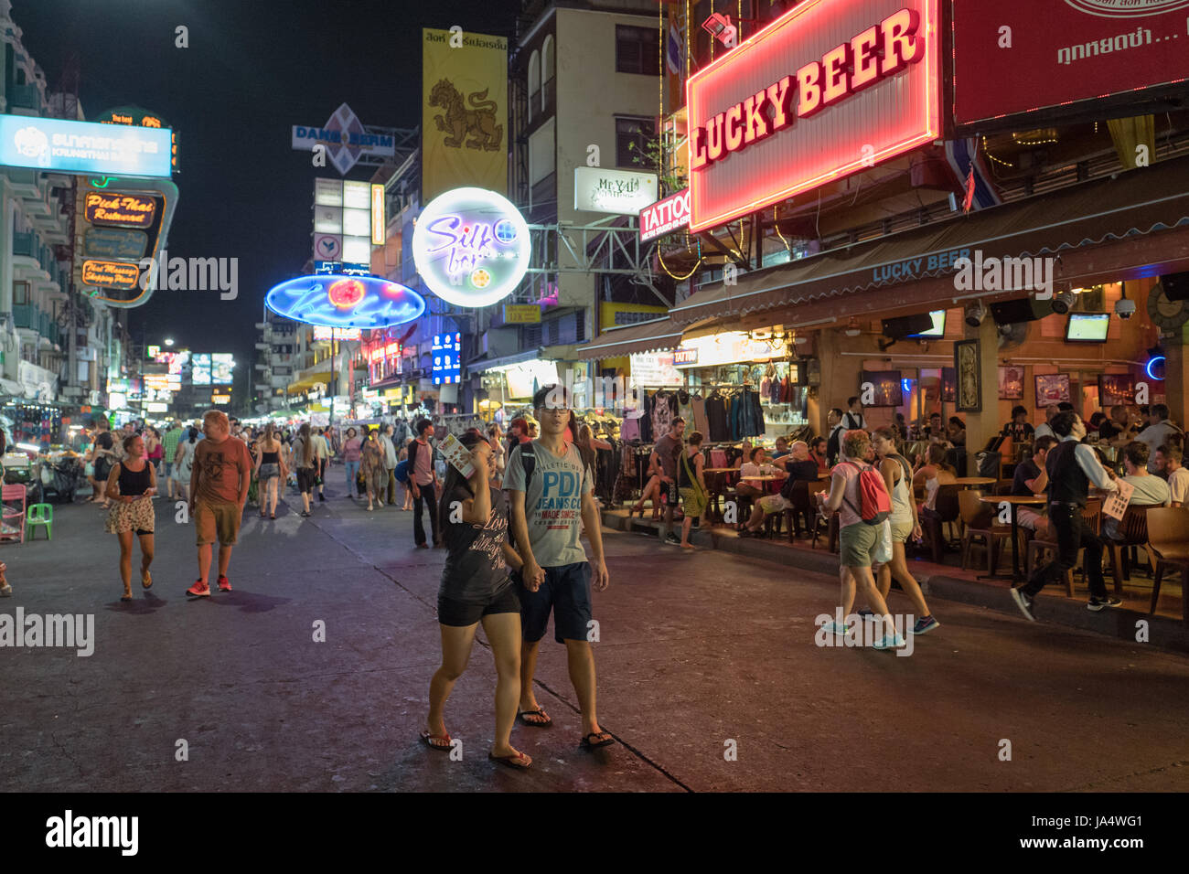 Khao San road by night in Bangkok. This is a world famous backpacker street and a major tourist attraction in Thailand. - Stock Image