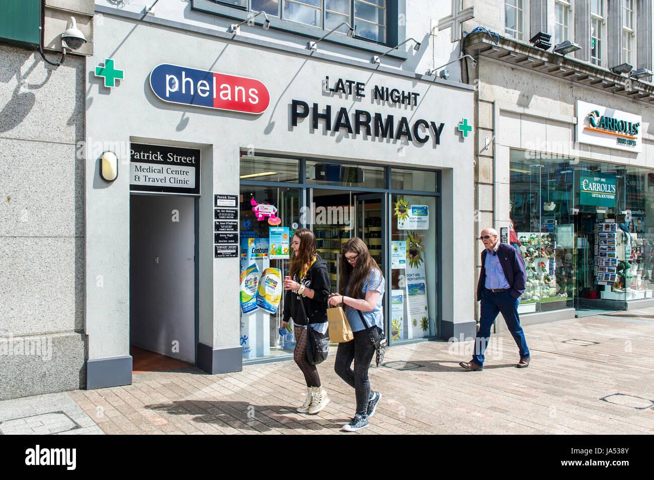 People walking past a late night pharmacy chemist on Patrick Street, Cork, Ireland. - Stock Image
