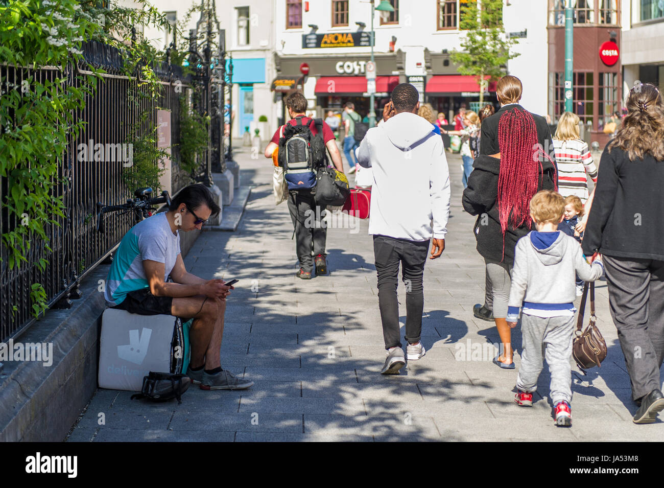 A Deliveroo Fast Food Delivery Rider uses his phone on a break in Cork, Ireland. - Stock Image