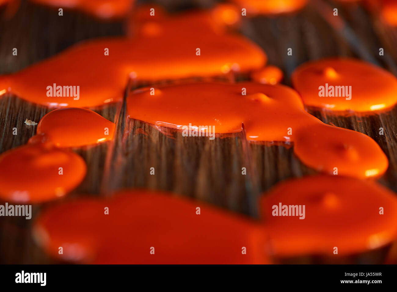 Drops frozen mirror glaze for decorating cakes and pastries.Orange food film - Stock Image