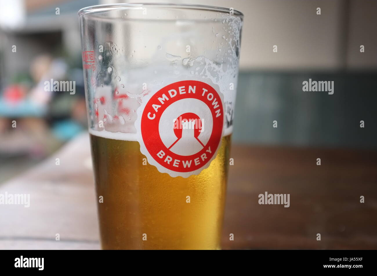 A pint glass with the logo of the Camden Town Brewery on it at a pub in Oxford, England, United Kingdom. June 2, - Stock Image