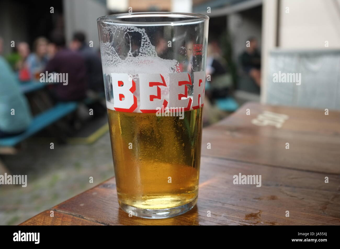 A pint glass with the word 'Beer' on it in the outside garden of a pub in Oxford, England, United Kingdom. - Stock Image