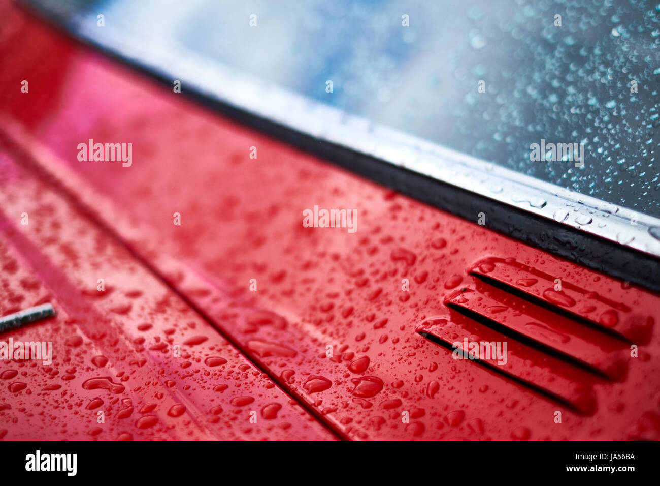 Rain falls on a red car forming water drops, close up of vent and window. Stock Photo