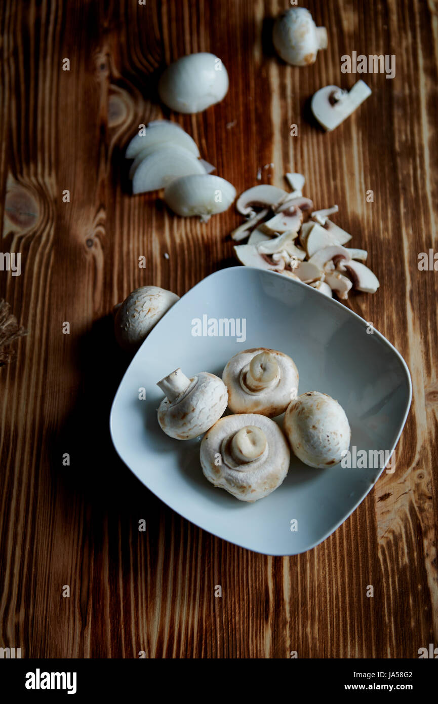 The process of cooking. mushrooms whole and sliced - Stock Image