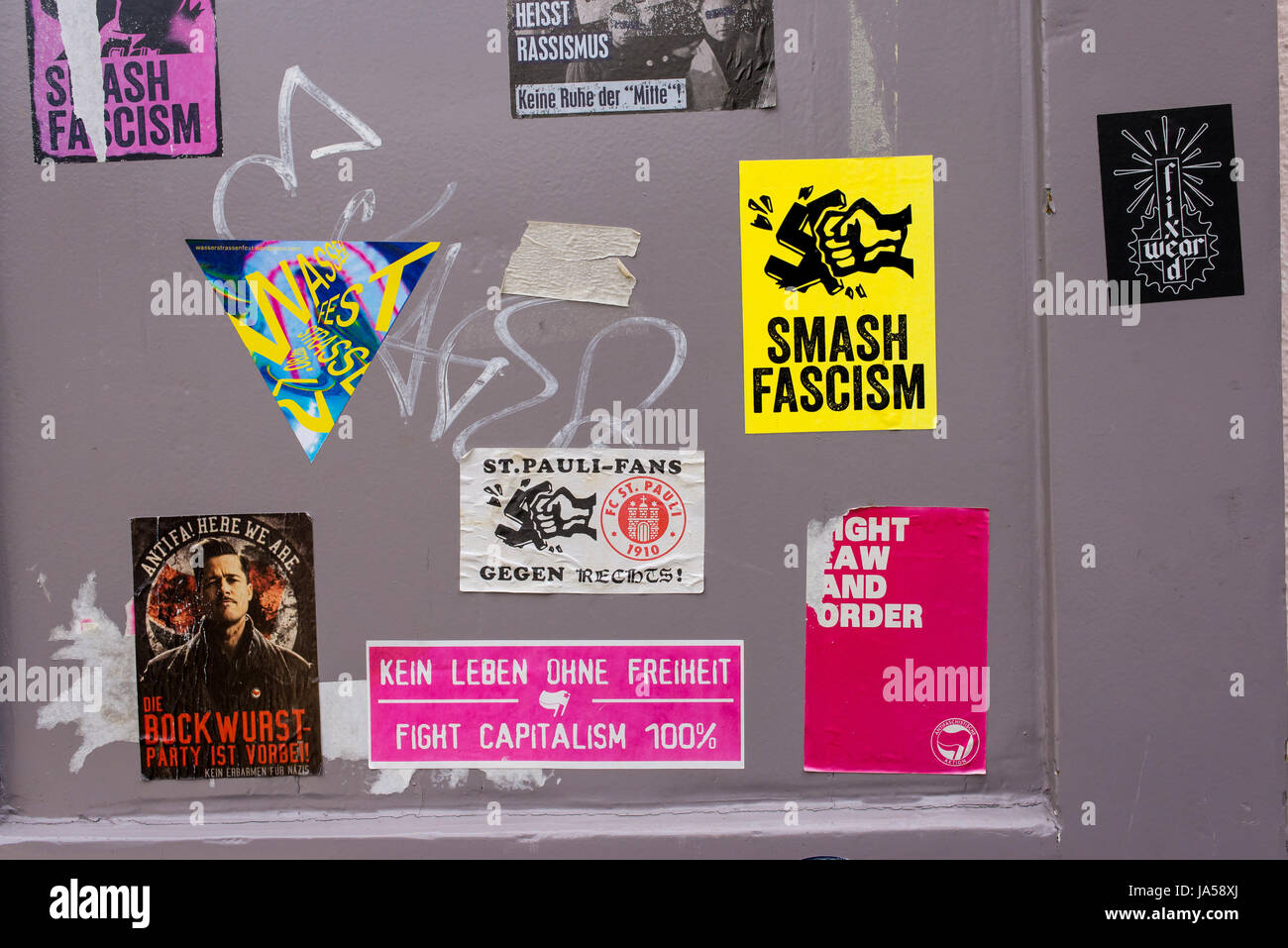 Anti fascism and fight capitalism stickers on a grey wall - Stock Image