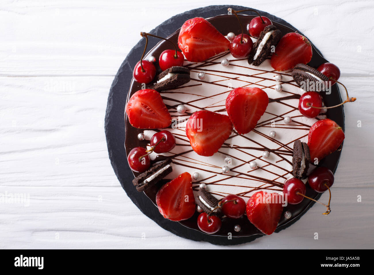 festive chocolate cake with strawberry and cherry close-up on the table. horizontal view from above - Stock Image