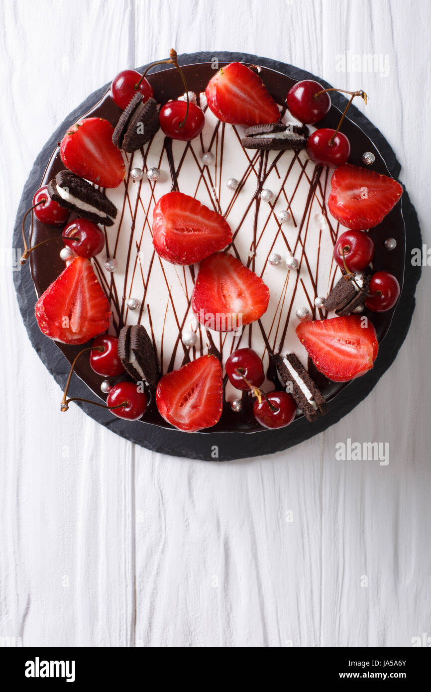 festive chocolate cake with strawberry and cherry close-up on the table. vertical view from above - Stock Image
